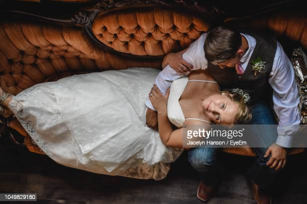 Portrait Of Smiling Bride With Groom Relaxing On Sofa At Home
