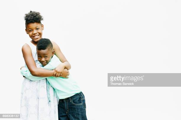 Portrait of smiling brother and sister embracing in front of white background