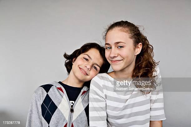 portrait of smiling brother (10-12) and sister (13-15), studio shot - schwester stock-fotos und bilder
