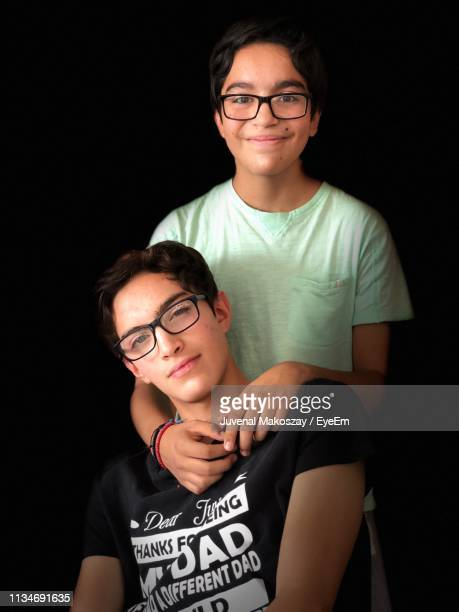 Portrait Of Smiling Brothers Against Black Background