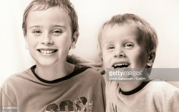Portrait Of Smiling Brothers Against Wall