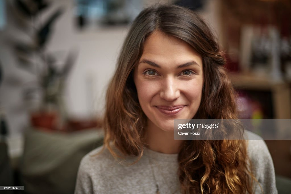 Portrait of smiling brunette woman at home : Stock Photo