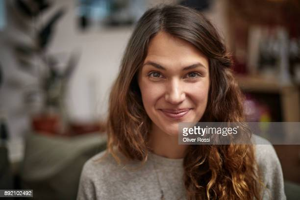 portrait of smiling brunette woman at home - smiling stock-fotos und bilder