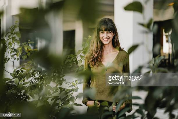 portrait of smiling brunette woman behind plants - khaki stock pictures, royalty-free photos & images