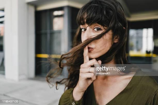 portrait of smiling brunette woman, finger on mouth - stilte stockfoto's en -beelden