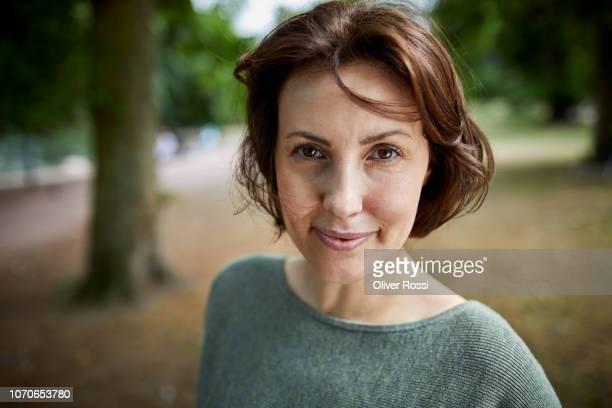 portrait of smiling brunette woman in a park - 40 44 años fotografías e imágenes de stock