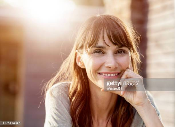 portrait of smiling brunette woman in backlight - gegenlicht stock-fotos und bilder