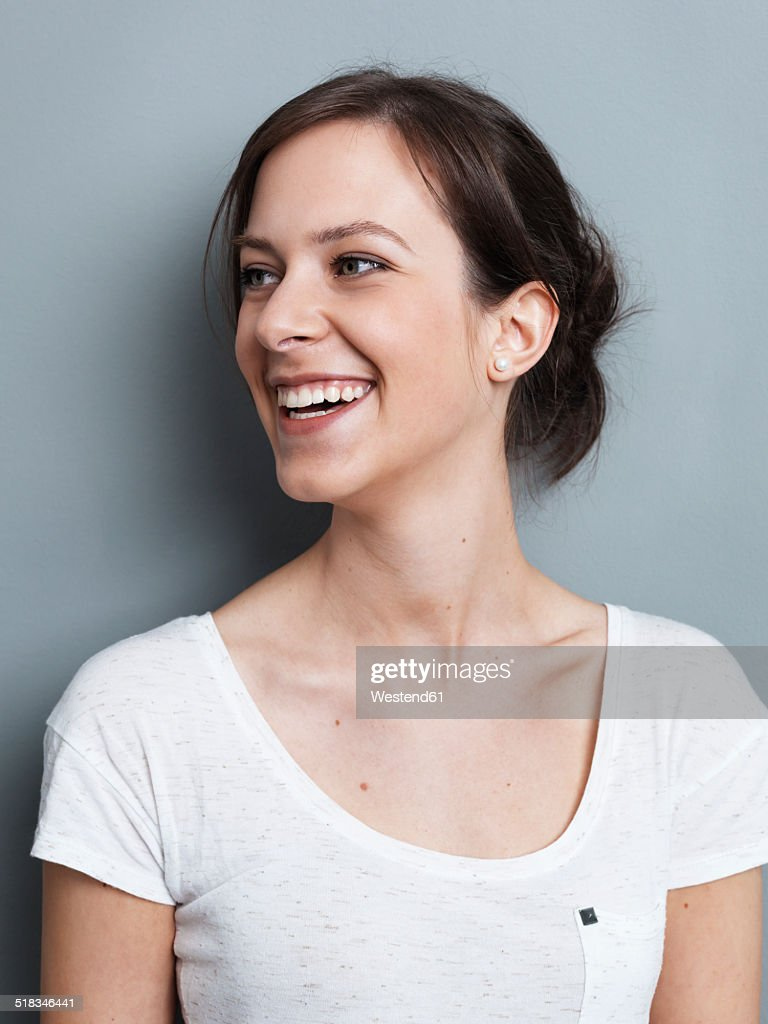 Portrait of smiling brunette woman in front of gray background : Stock Photo