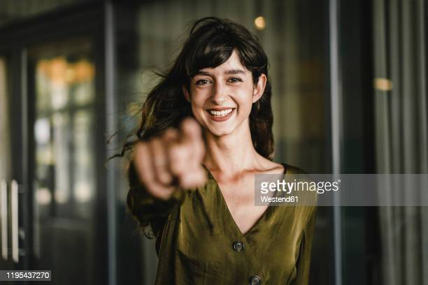 portrait of smiling brunette woman - mit dem finger zeigen stock-fotos und bilder