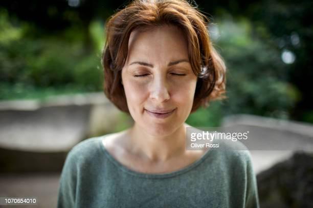 portrait of smiling brunette woman with closed eyes in a park - augen geschlossen stock-fotos und bilder