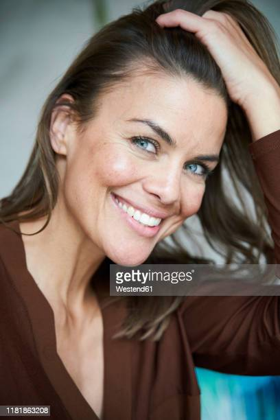 portrait of smiling brunette woman with hand in hair - one mature woman only stock pictures, royalty-free photos & images