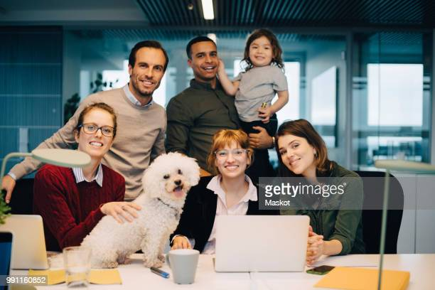 Portrait of smiling business team with kid and dog at creative office