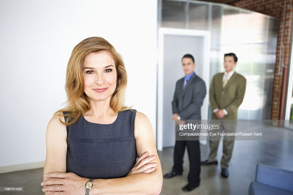 Portrait of smiling business woman in foreground : Stock Photo