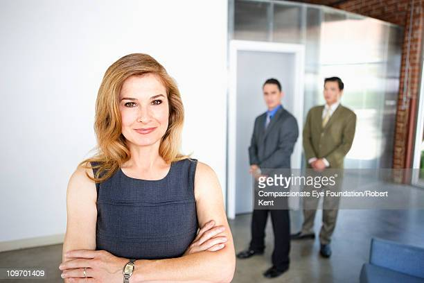 """portrait of smiling business woman in foreground - """"compassionate eye"""" stock pictures, royalty-free photos & images"""