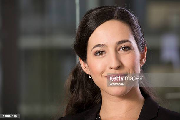 Portrait of smiling business woman in front of glass pane