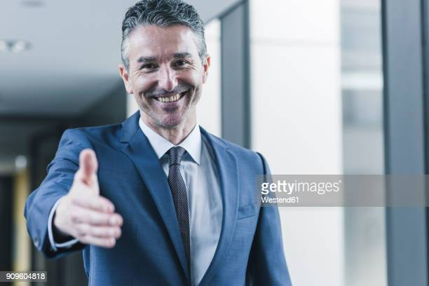 portrait of smiling businessman about to shake hands - greeting stock-fotos und bilder