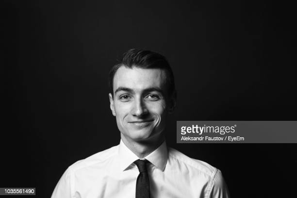 portrait of smiling businessman against black background - blanco y negro fotografías e imágenes de stock