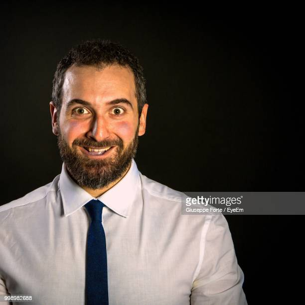 Portrait Of Smiling Businessman Against Black Background