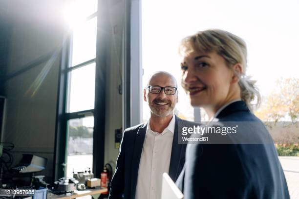 portrait of smiling businessman and businesswoman at the window in a factory - business stock-fotos und bilder