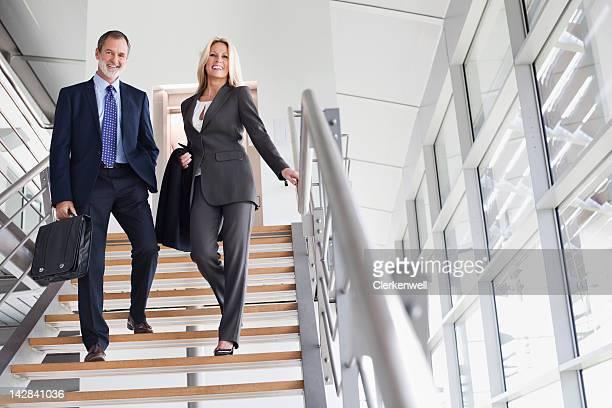 Retrato de sorridente Empresário e Mulher de Negócios sobre escadas
