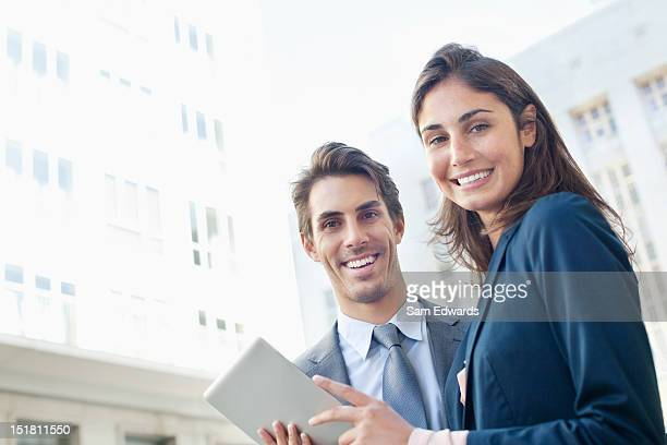Portrait of smiling businessman and businesswoman with digital tablet