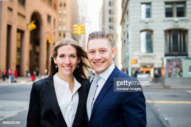 portrait of smiling businessman and woman standing on city street - geschäftskleidung stock-fotos und bilder