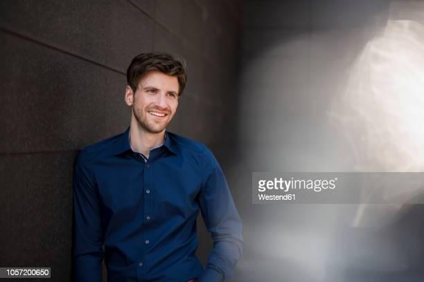 portrait of smiling businessman at a wall - oberkörperaufnahme stock-fotos und bilder