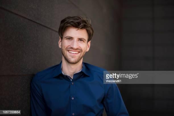 portrait of smiling businessman at a wall - junger mann allein stock-fotos und bilder