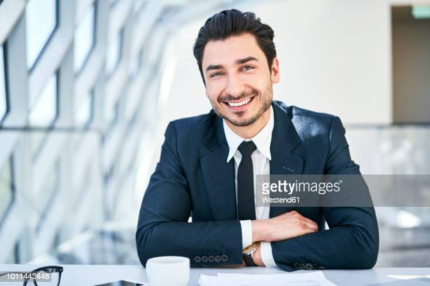 Portrait of smiling businessman at desk in modern office