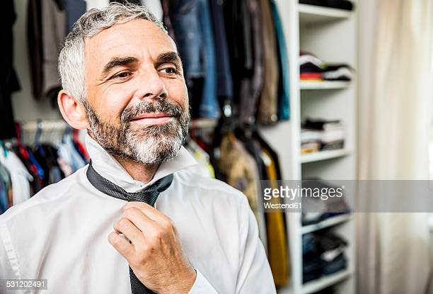 portrait of smiling businessman binding tie at his walk-in closet - walk in closet stock photos and pictures