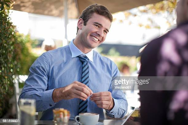 Portrait of smiling businessman drinking coffee with business partner
