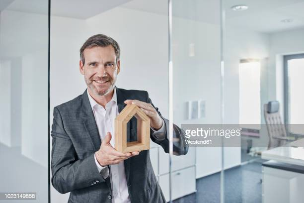 Portrait of smiling businessman holding architectural model in office