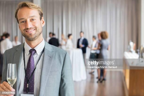 Portrait of smiling businessman holding champagne flute