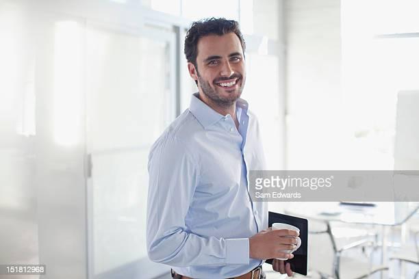 portrait of smiling businessman holding coffee cup in office - 30 34 jaar stockfoto's en -beelden