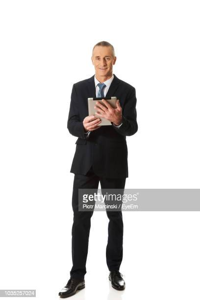 portrait of smiling businessman holding digital table while standing against white background - full suit stock pictures, royalty-free photos & images