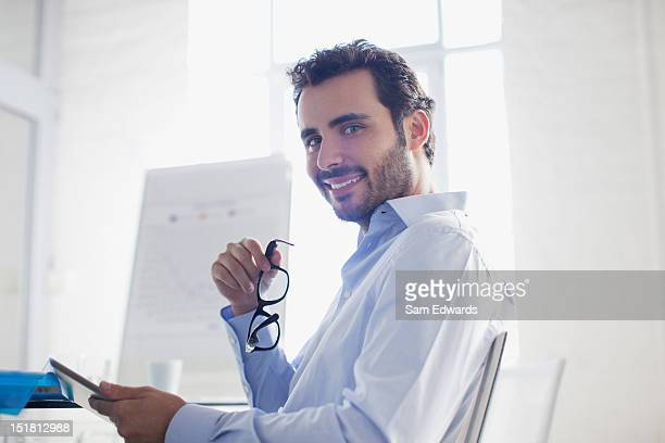 Portrait of smiling businessman holding eyeglasses and digital tablet in office