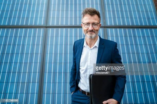 portrait of smiling businessman holding folder standing in front of solar panels - ingenieur stock-fotos und bilder