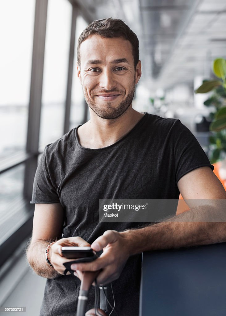 Portrait of smiling businessman holding mobile phone while leaning on cubicle in office : Stock Photo