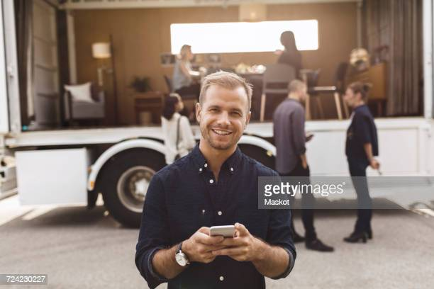 Portrait of smiling businessman holding mobile phone with colleagues and portable office truck on road in background