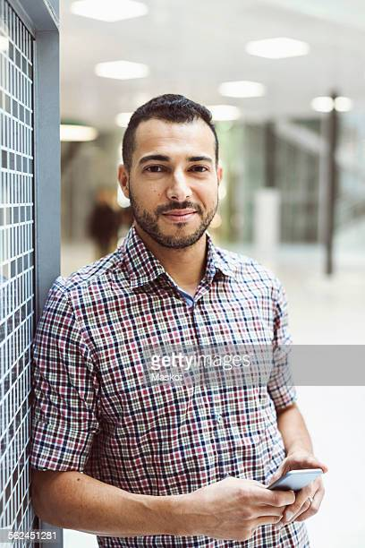 portrait of smiling businessman holding smart phone while leaning on wall in office - homme maghrebin photos et images de collection
