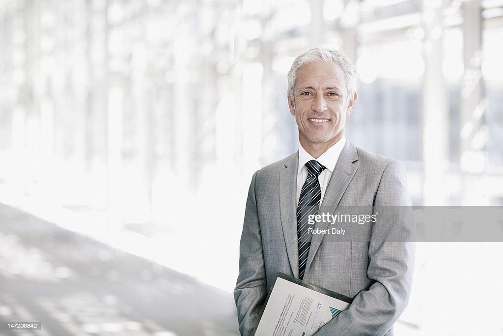Portrait of smiling businessman in corridor : Stock Photo