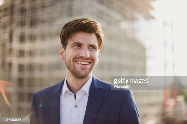 portrait of smiling businessman in front of construction site looking sideways - gegenlicht stock-fotos und bilder