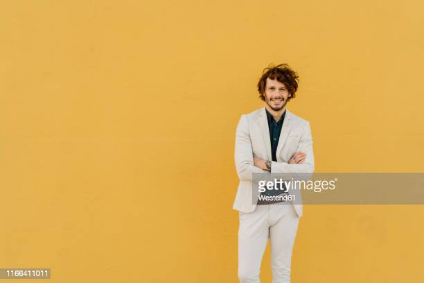 portrait of smiling businessman in front of yellow wall - ジャケット ストックフォトと画像