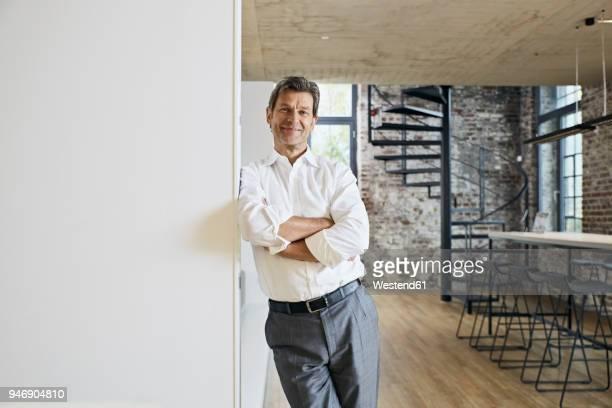 portrait of smiling businessman in modern office - lehnend stock-fotos und bilder