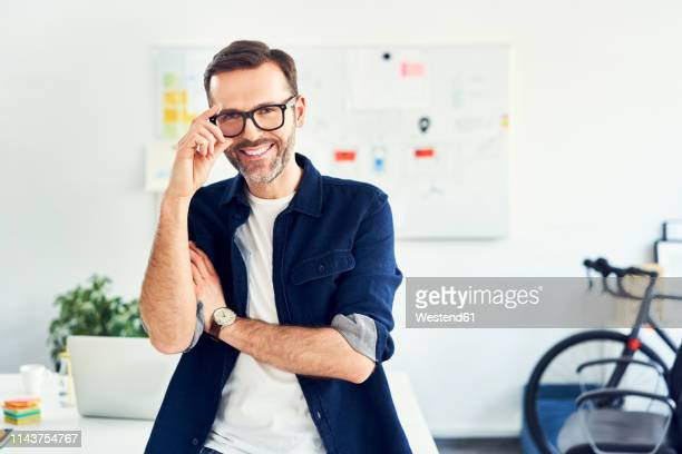 portrait of smiling businessman in office - design professional stock pictures, royalty-free photos & images