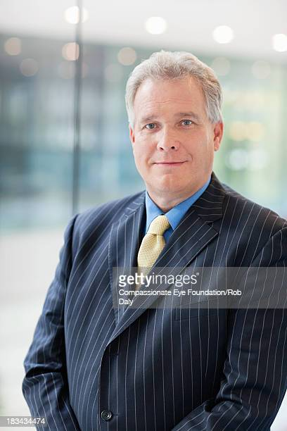 """portrait of smiling businessman in office - """"compassionate eye"""" stock pictures, royalty-free photos & images"""