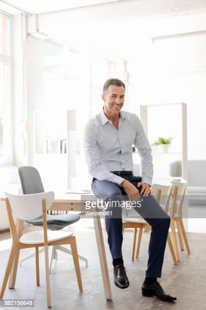 portrait of smiling businessman in office - sitting stock-fotos und bilder