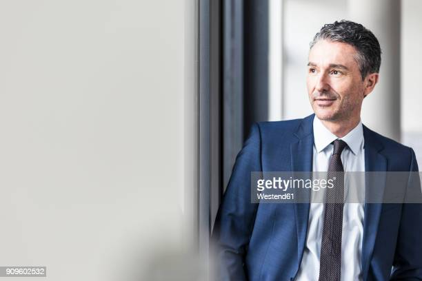 portrait of smiling businessman in office - anzug stock-fotos und bilder
