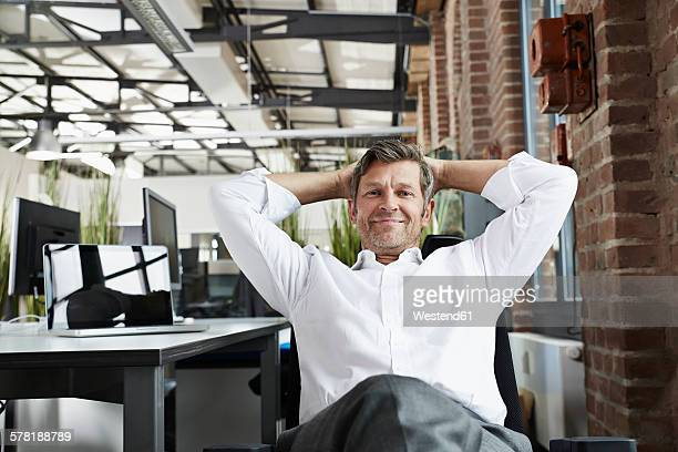 Portrait of smiling businessman in office relaxing