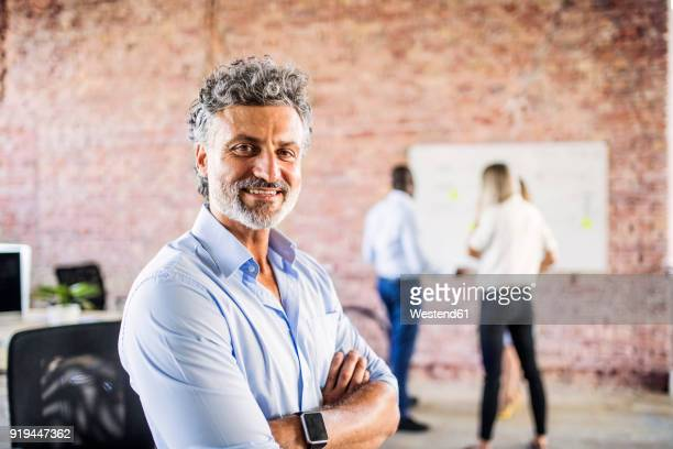portrait of smiling businessman in office with colleagues in background - onscherpe achtergrond stockfoto's en -beelden